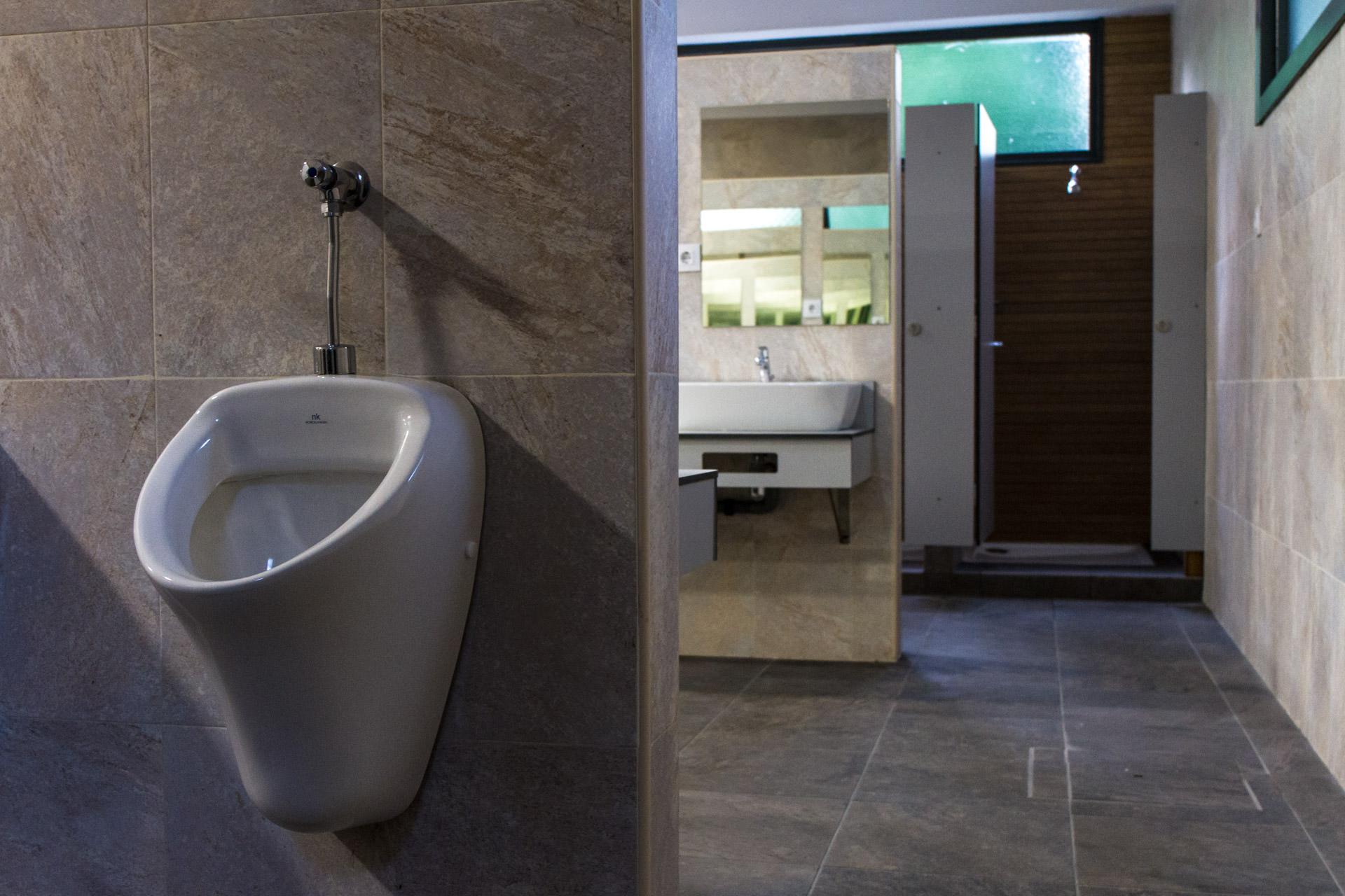 Urinario, lavabo y ducha al fondo, instalaciones del a zona de asesos