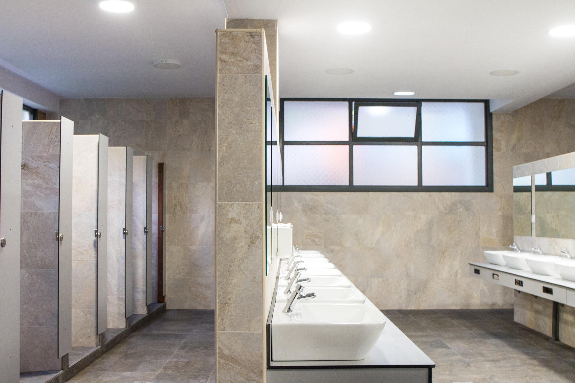 Vista interior de las baños del camping con duchas y lavabos