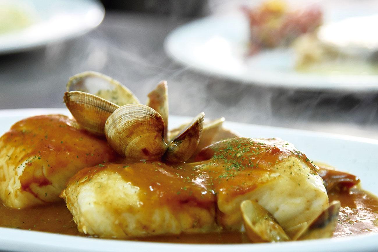 Plato humeante de pescado con almejas a disfrutar en la Cafetería del Camping Las Hortensias