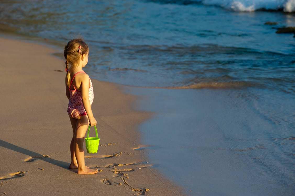 Niña con cubo mira el mar desde la orilla de la playa