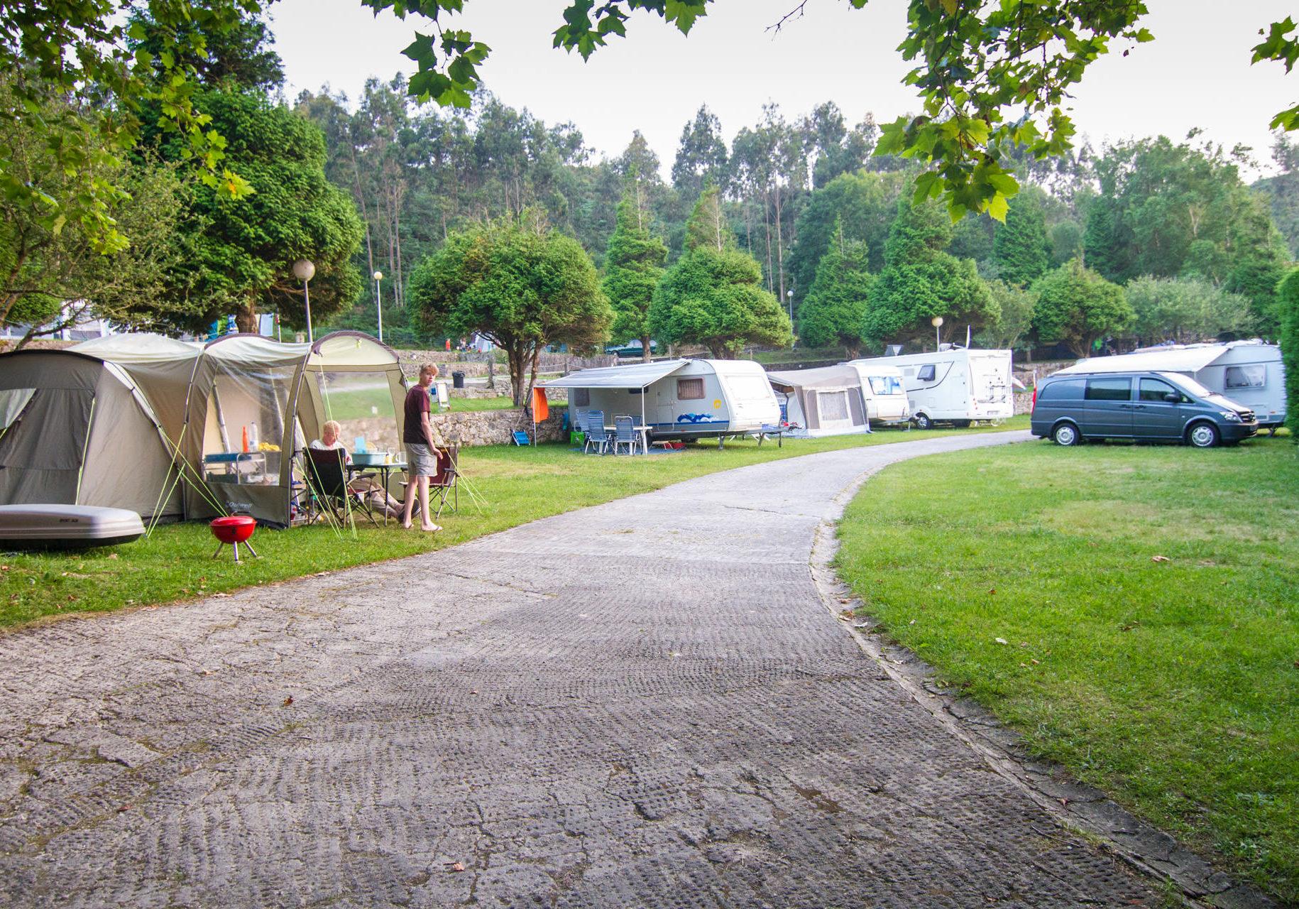 Vista interior del camping con caravanas, tiendas de campaña y vehículos